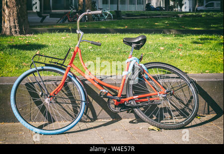 Orange color bicycle. Bike unlocked leaned on a sidewalk wall in Rotterdam city, Netherlands - Stock Photo