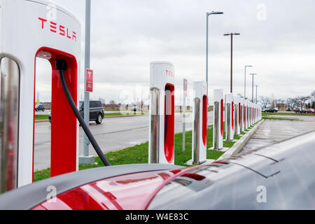 Tesla Model S plugged-in, charging at Tesla Supercharger Stall seen over the rear spoiler / windshield. - Stock Photo