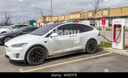 White Tesla Model X charging with Model S alongside at Vaughan Mills Tesla Supercharger location. - Stock Photo