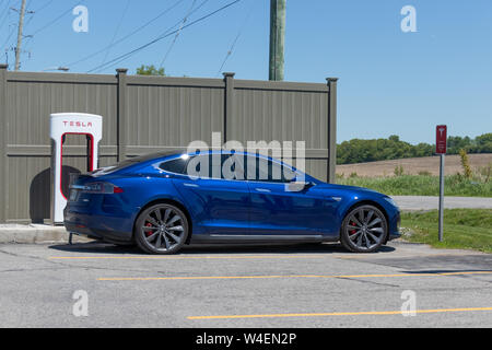 Metallic Blue Tesla Model S parked, charging at Tesla Supercharger in Port Hope, Ontario. - Stock Photo