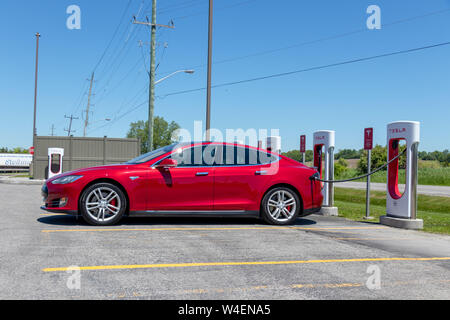 Tesla Model S parked at Tesla Supercharger Station, plugged-in and charging. - Stock Photo