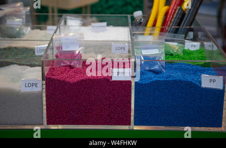 Colorful of dyed plastic polymer granules in containers - Stock Photo