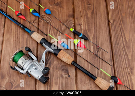 KYIV, UKRAINE - MAR 19, 2019: Fishing tackle - fishing rod fishing float and lures on beautiful blue wooden background, copy space. - Stock Photo