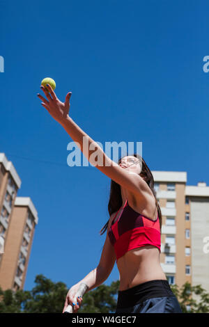 Female tennis player playing on court in the city - Stock Photo