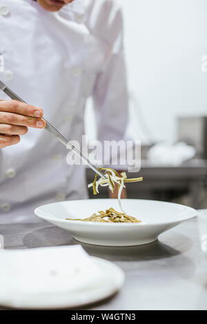 Junior chef prepairing a meal on plate - Stock Photo