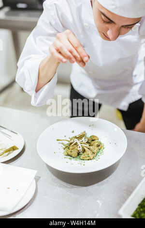 Junior chef prepairing a dessert on plate - Stock Photo