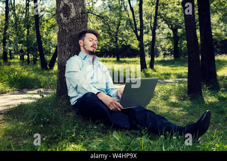 Young man with blue shirt working on his laptop in a public park sitting on the ground Selective focus - Stock Photo