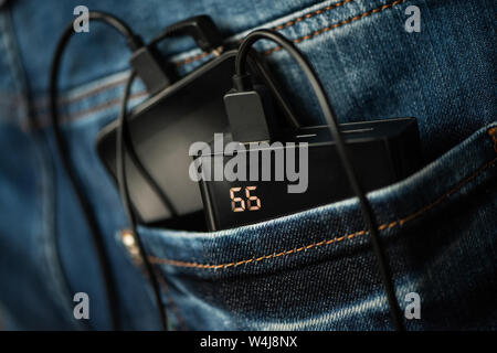 There are a power bank and smartphone in the back pocket of jeans. - Stock Photo