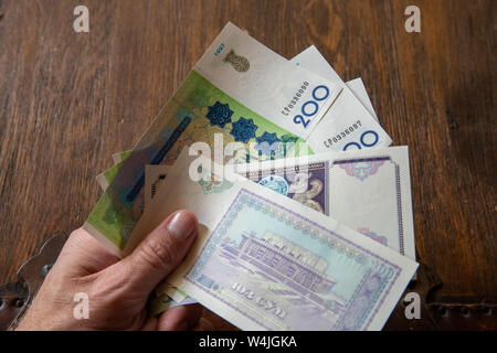 Hand Holding Uzbekistani money, known as So'm. - Stock Photo