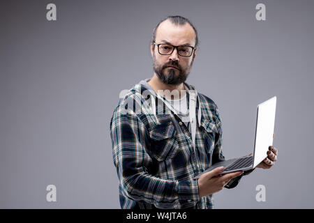 Bearded man wearing glasses standing staring intently at the camera holding a laptop with an expectant puzzled expression isolated on grey with copy s - Stock Photo