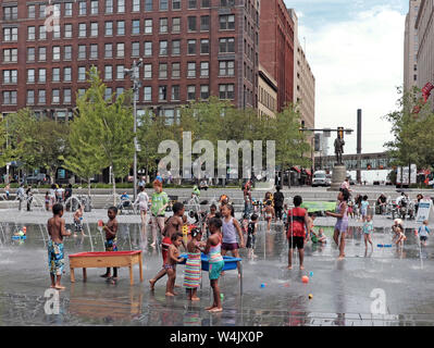 Children play in the water fountains of Public Square in downtown Cleveland, Ohio, USA during the summer. - Stock Photo