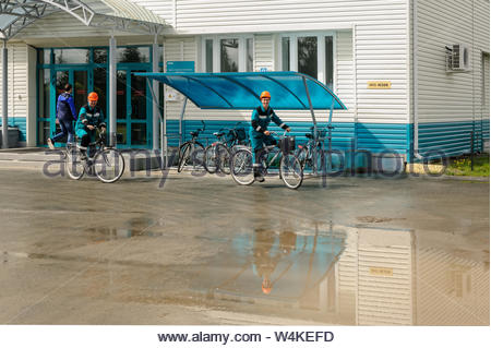 Tobolsk, Russia - July 15. 2016: Sibur company. Men in working uniform move by bicycle - Stock Photo