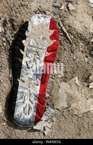 The flag of Yemen is depicted on the sole of an old boot. Ecology concept with environmental pollution from household and industrial waste. - Stock Photo