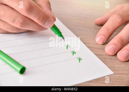 Concept of hand with green marker pen filling out a questionnaire on a sheet of paper on a wooden table. Horizontal composition. Elevated view. - Stock Photo