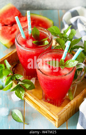 Cold Watermelon Smoothie. Summer Watermelon drink in glasses and slices of watermelon on rustic wooden table. - Stock Photo