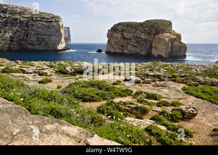 Scenic view of cliffs, fungus rock and blue ocean at dweira bay with green vegetation in gozo, malta. - Stock Photo
