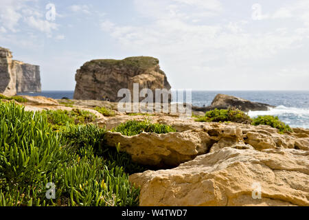 Scenic view of beautiful green vegetation and cliffs, fungus rock and blue ocean at dweira bay in gozo, malta. - Stock Photo