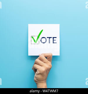 hand holding white paper with the 'vote' and green check mark voting symbols in checkbox of the inscription isolated on blue background - Stock Photo