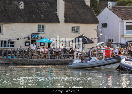 Customers drink outside the Pandora Inn at high tide in Restronguet Creek - Stock Photo