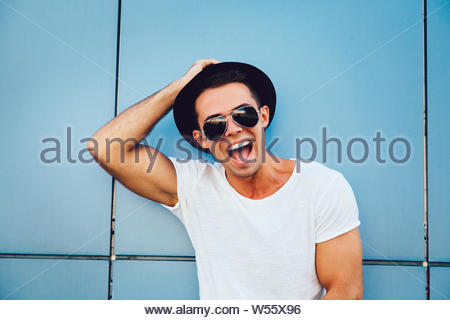 Portrait of a cheerful muscle guy in sunglasses and hat looking at camera and smiling widely, posing outdoors. Dressed in white t-shirt. - Stock Photo