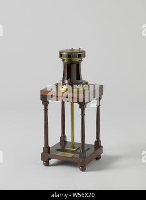 Model of a Capstan, Model of a capstan in a two-level wooden frame. The capstan is for eight wind trees and has six catches in the heel to prevent it from walking back. The metal king continues into a trail on the lower deck. This capstan has two speeds, which are obtained by lowering or lifting the catches in the head and in the heel, the gear, consisting of sun and planetary wheels, is placed under the upper deck between the beams of the fishing., anonymous, c. 1819, wood (plant material), brass (alloy), model: h 26 cm × l 14.5 cm × w 14.5 cm packaging capsule: h 51.5 cm × w 73 cm × d 25.5 - Stock Photo