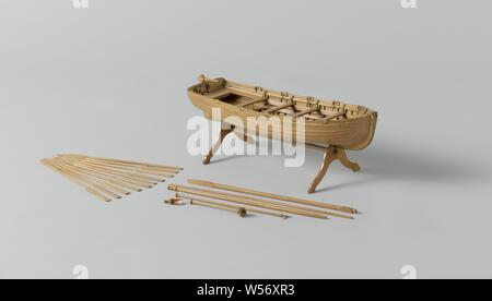 Model of an Armed Longboat, Truss model with round timber. Smooth-edged double-belted barkas, round truss with flat sheer and flat mirror, a forecourt, four diets and rails and an open cabin with side dents. The prow is provided with a disk. Three-part frames. Simple rudder with a tiller that fits over the rudder king. The rig consists of a large mast with ra for a bucket sail and a grape mast with a parrot pole and whip. On separate parts there is also a hand pump, a boat hook and ten oars. 1:20 scale (derived)., Rijkswerf Rotterdam, Rotterdam, c. 1819, wood (plant material), brass (alloy) - Stock Photo