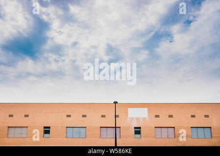 Facade of an unrecognizable brick building with three quarters of sky with blue clouds in the background, copy space. - Stock Photo