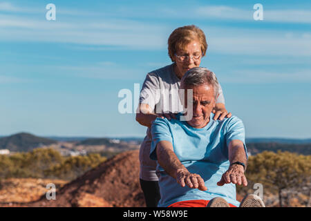 Senior woman help the elderly man while doing a stretching exercise outdoors with blue sky background - Stock Photo