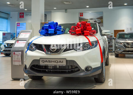 ST. PETERSBURG, RUSSIA - JULY 09, 2019: The sold car Nissan Qashqai (2019) with two bows of red and blue color in car showroom - Stock Photo