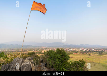 Flag fluttering atop the Pha Poak hill. Beautiful view of fields, Vang Vieng town and mountains from above in Laos, on a sunny day. Copy space. - Stock Photo