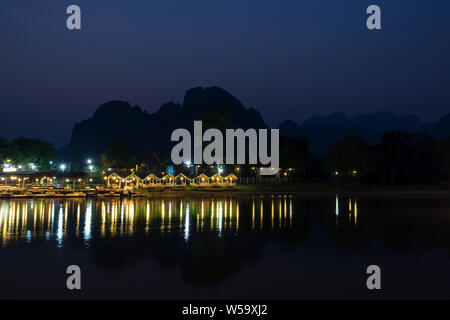 Few people sitting at a lit waterfront restaurant by the the Nam Song River and silhouette of karst limestone mountains in Vang Vieng, Laos, at dusk. - Stock Photo