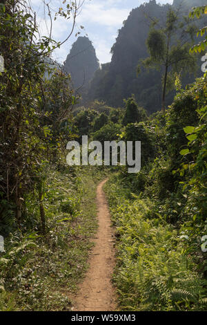 Scenic view of a lush nature, limestone mountains and hills - Off the beaten path near Vang Vieng, Vientiane Province, Laos, on a sunny day. - Stock Photo