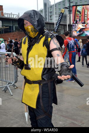 Attendees at the MCM Comic Con pop culture convention in Manchester, uk, July 27, 2019, at the start of a two day event where many participants dress up as their favourite superhero, anime, villain or pokemon character. The event attracts thousands of sci- fi enthusiasts, comic collectors, fantasy and game fans to the Manchester Central Convention Centre in city centre Manchester. - Stock Photo