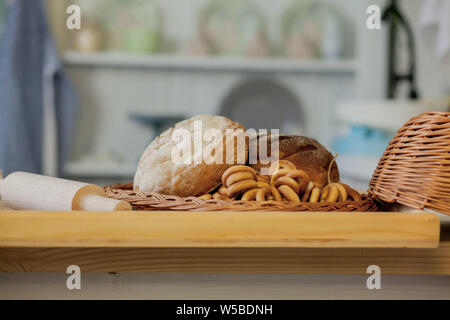 Assortment of breads near a wicker basket on a table in a rustic kitchen. Composition in kitchen at the photo studio. - Stock Photo