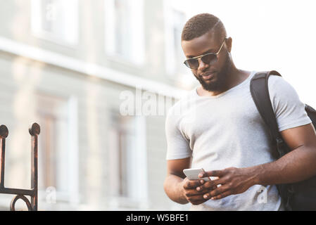 Concentrated african man checking flying departure online - Stock Photo