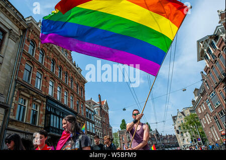 A man waves a rainbow flag during the Pride Walk.Because of the Stonewall 50th anniversary, the Pride Walk theme this year is 'Remember the past, create the future'. The Pride Walk is a demonstrative and activist walk from the Homomonument to the Vondel Park. This is the 'counterpart' of the world-famous boat parade that takes place a week later on August 5th. Thousands of people participated by carrying the flags of the countries where homosexuality is in the Penal Code. - Stock Photo