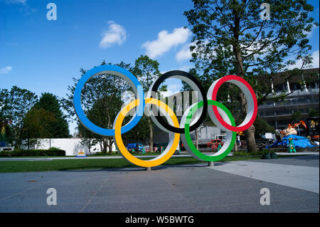 Tokyo, Japan. Olympic rings in front of the new national stadium of Tokyo in representation of the 2020 olympics. - Stock Photo
