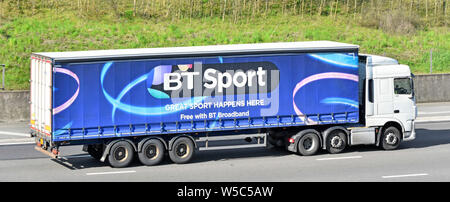 BT Sport advertising on side of blue articulated trailer behind white hgv lorry truck as free with British Telecom broadband vehicle on UK motorway - Stock Photo