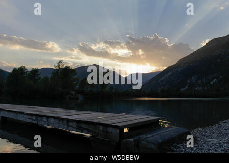 Light rays during the golden hour above a lake in south france - Stock Photo
