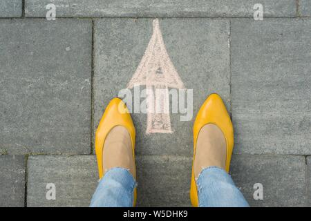 Female feet with arrow painted on the grey sidewalk. - Stock Photo
