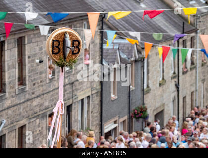 Langholm, Dumfries and Galloway, Scotland, UK. 26th July 2019. The Barley Bannock is held aloft during the walk up the Kirk Wynd. - Stock Photo