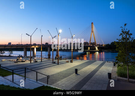 Vistula River Boulevard with Swietokrzyski Bridge at dusk in city of Warsaw in Poland. - Stock Photo