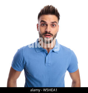 Confused man wearing a light blue polo being surprised while looking at the camera on alight background - Stock Photo