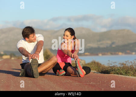 Couple of runners stretching legs after sport sitting on the road - Stock Photo
