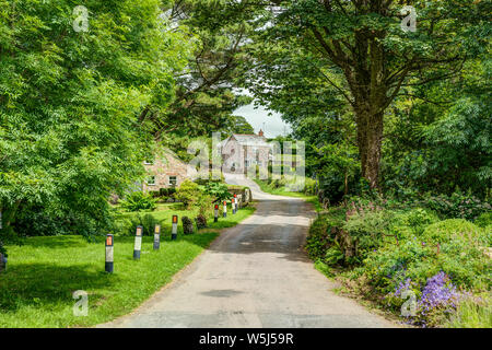 An idyllic landscape of a typical English country village in summertime. A winding tree lined lane over a small bridge with a cottage in the distance - Stock Photo