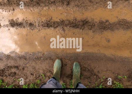 Farmer in rubber boots standing on muddy dirt road in countryside, feet from above - Stock Photo