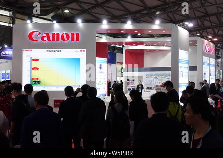 --FILE--People visit the stand of Canon during an exhibition in Shanghai, China, 19 March 2019.   Canon, the Japanese multinational imaging and optica - Stock Photo