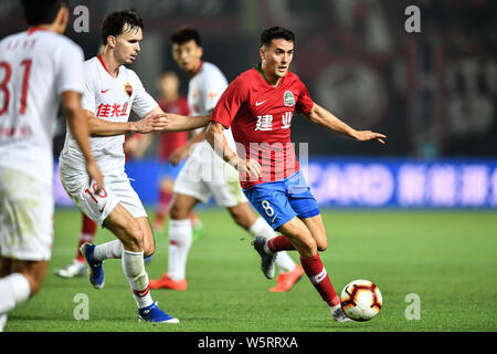 English-born Taiwanese football player Tim Chow, right, of Henan Jianye passes the ball against Norwegian football player Ole Selnaes of Shenzhen F.C. - Stock Photo