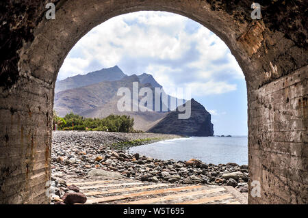 Rocky beach with the mountainous cliff of roque de las Marciegas viewed from the walking tunnel to the port. Eastern part of Gran Canaria. Placed in L - Stock Photo