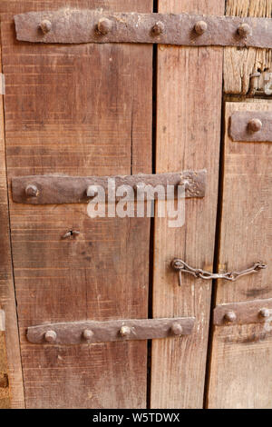 Old wooden entrance gate with iron fittings on the grounds of Humayun's Tomb, Delhi, India - Stock Photo